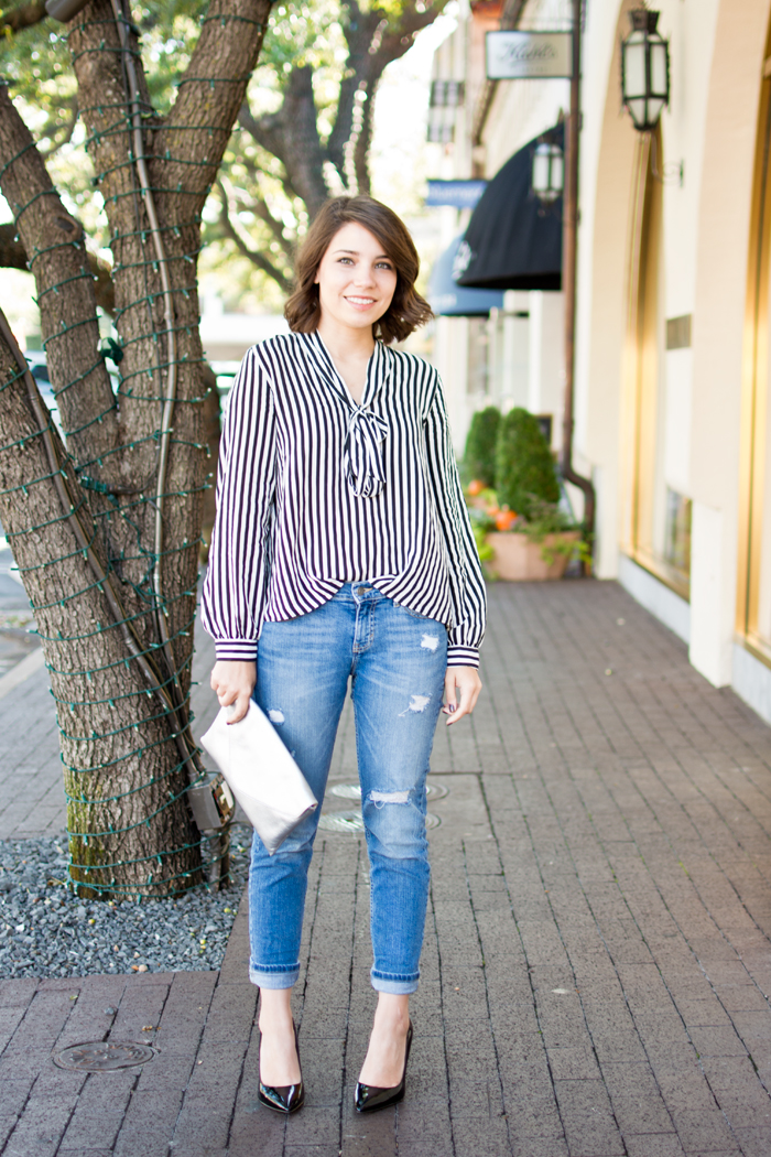 Fashion blogger black and white stripe blouse with silver clutch, black heels and boyfriend jeans