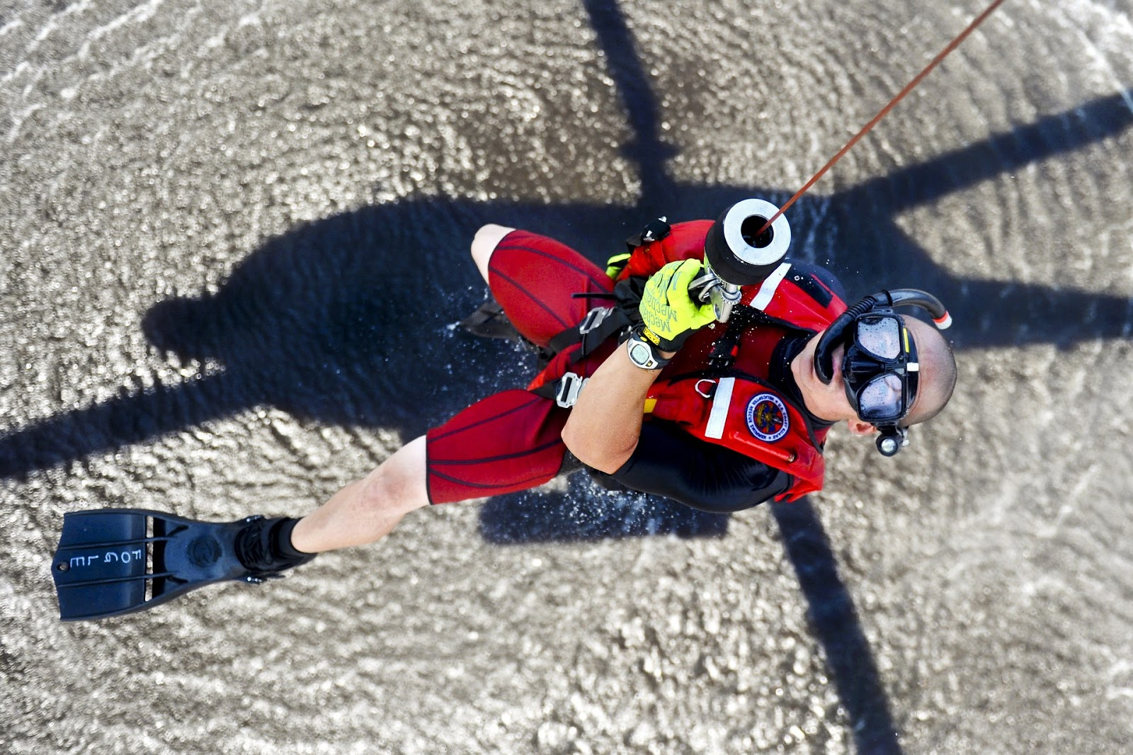 coast guard rescue swimmer is lowered into the ocean from a helicopter to illustrate a blog post about rescue mission movies