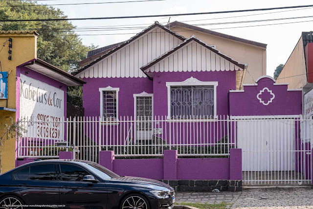 Casa pintada com cores de tons contrastantes, o que destaca os elementos decorativos