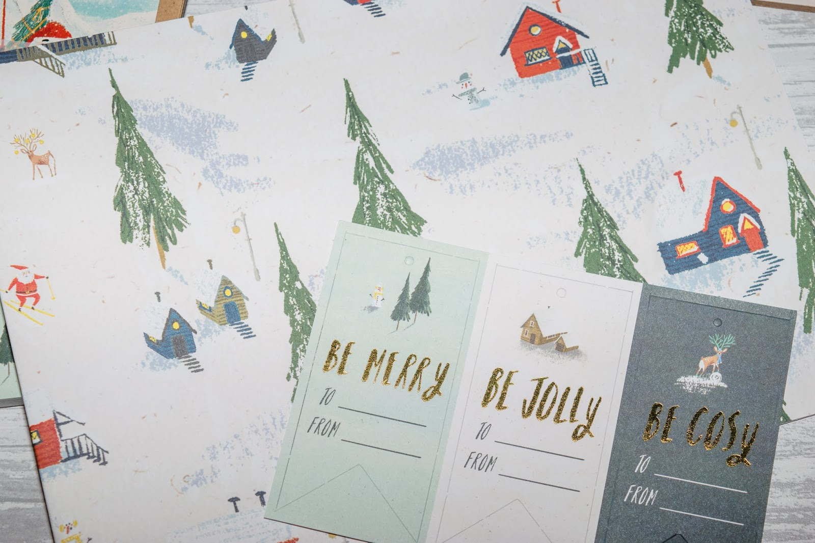 Wrapping paper with a snowy forest scene printed on and snowy buildings. Three Christmas tags with the same design are on top.