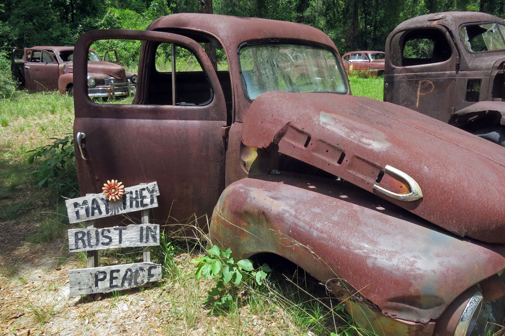 Rusty vehicles on display in Florida field.
