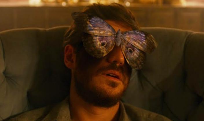 Imagem: Rosto do personagem Eric com uma borboleta pousada em seu nariz, cobrindo seus olhos.