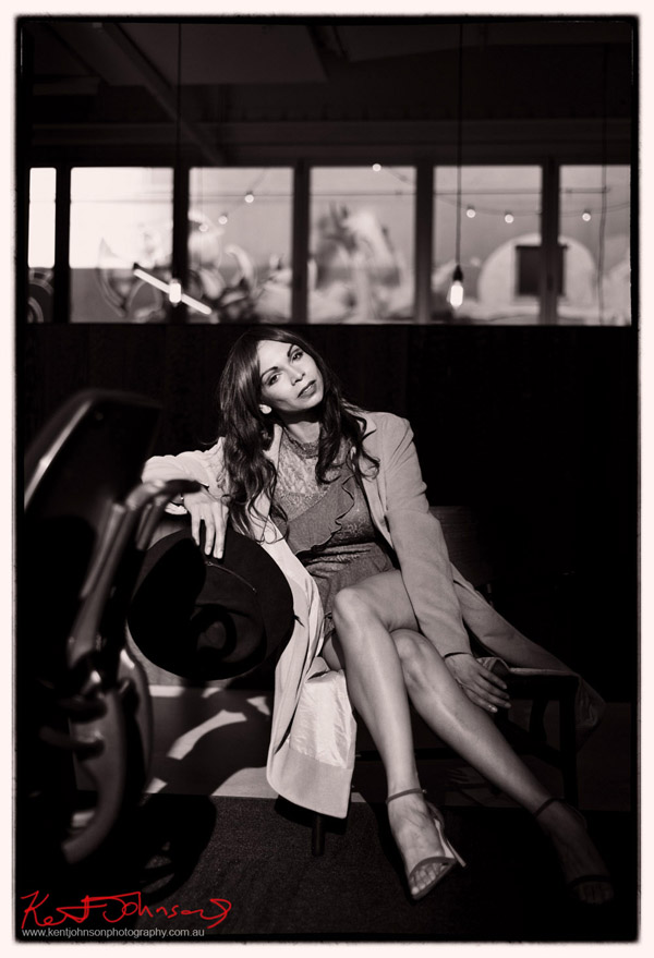 Black and white portrait of a seated model in a long coat with beautiful long legs for a modelling portfolio. Photographed by Kent Johnson, Sydney, Australia.