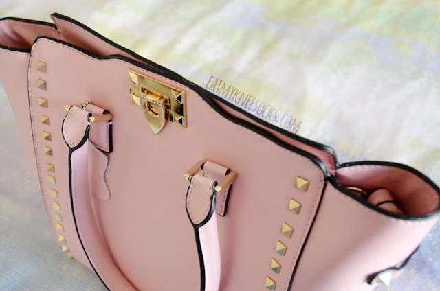 Details on the pastel pink Rockstar leather bag from BagInc, featuring gold studs, rivets, and hardware along with multiple straps on a 100% real calf skin fabric.