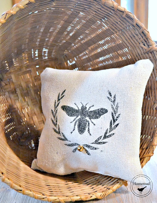 stenciled bee pillow in a basket