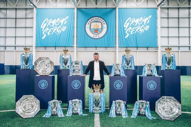 Sergio Aguero pose with Man City trophies