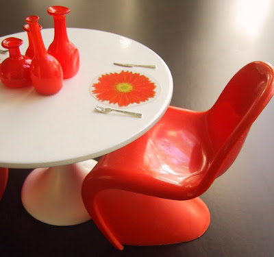 Modern dolls' house miniature Sarinnen table and orange Panton chair. On the table are some orange glass bottles and a place mat in the shape of a flower.