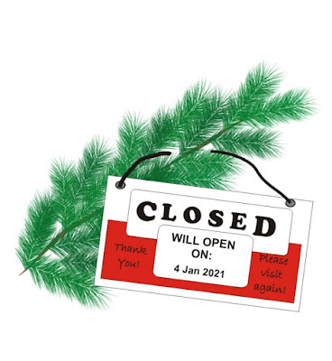 sign saying: Closed, open on 4 January, hanging on a pine branch