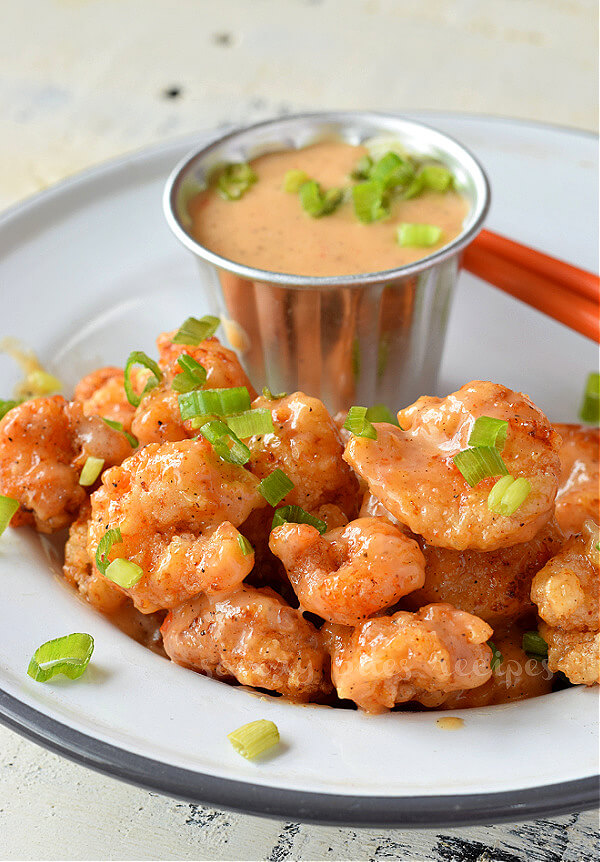a close look of a white plate with crispy bang bang shrimp topped with chopped spring onion