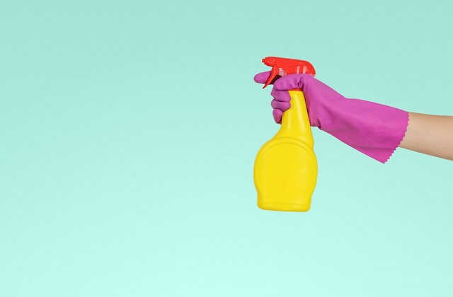 hand with pink gloves yellow spray bottle green wall