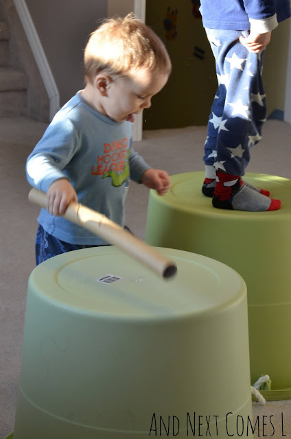 Toddler drumming on a plastic bucket with a cardboard tube