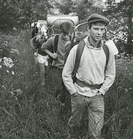 A group of men wearing backpacks, walking in a line.