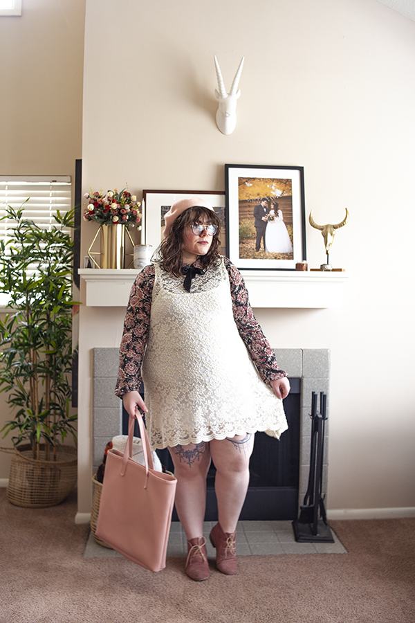 An outfit consisting of a pastel pink beret, a black and pink Peter Pan collared dress layered under a sleeveless cream lace dress pastel pink desert boots and a pink tote bag.