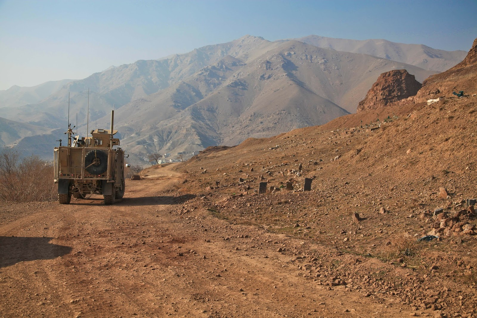 a military armored vehicle drives down a barren dirt road in afghanistan for blog post about documentaries restrepo and korengal