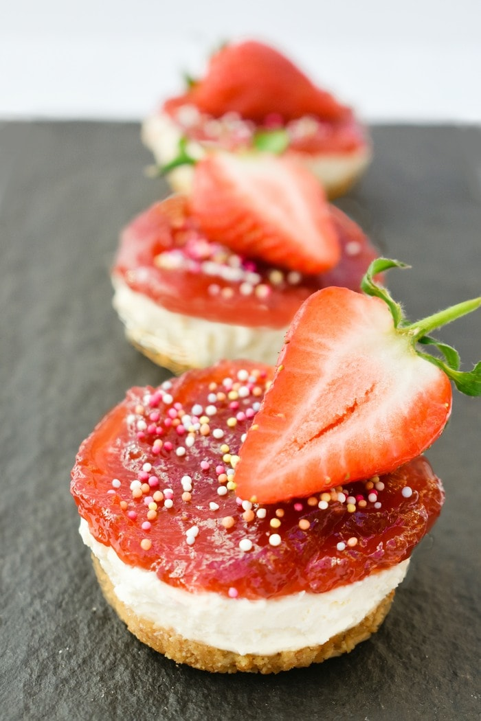3 Mini Strawberry Cheesecakes on a slate board