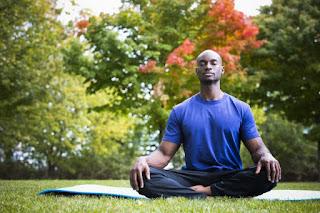 man sitting cross-legged on a yoga mat outside