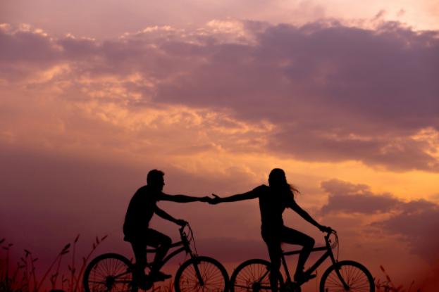A silhouette of a two people on bicycle