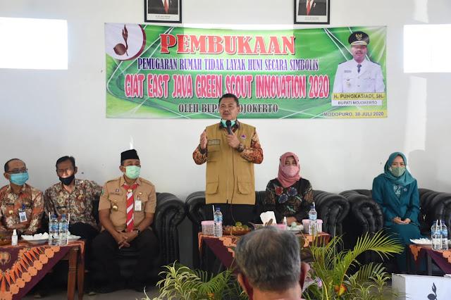 """Mojokerto - Bupati Mojokerto Pungkasiadi yang juga Ketua Majelis Pembimbing Kwartir Cabang (Kamabicab) Gerakan Pramuka Kabupaten Mojokerto, memimpin pembukaan pemugaran rumah tidak layak huni (rutilahu) secara simbolis dalam giat East Java Green Scout Innovation (EJGSI) 2020 di Desa Modopuro Kecamatan Mojosari, Kamis (30/7) siang.  """"Kami laporkan bahwa ada delapan rumah tidak layak huni yang dipugar, dengan alokasi dana Rp 50 juta per rumah. Program direncanakan selesai bulan September, dengan disertai beberapa rangkaian penyerahan. Antara lain 100 tempat sampah, 150 sembako, gerobak sampah, pembangunan gapura, dengan seluruh total alokasi dana yang disumbangkan senilai Rp 500 juta,"""" jelas Didik Chusnul Yakin selaku Ketua Kwatir Cabang Gerakan Pramuka Kabupaten Mojokerto.  Kamabicab Gerakan Pramuka Kabupaten Mojokerto Pungkasiadi, pada arahannya mengaku sangat mengapresiasi EJGSI 2020. Dirinya juga berharap agar Gerakan Pramuka terus dibangkitkan agar makin kreatif, mandiri dan bermanfaat.     """"Ayo kita bangkitkan terus Gerakan Pramuka. Kita bangkitkan lagi kemandiriannya. Kita kembalikan lagi seperti dulu. Tiap Jum'at Sabtu pakai baju Pramuka. Organisasi ini sangat positif, dan baik untuk diikuti sejak dini. Saya mengapresiasi dan berterima kasih kepada teman-teman Pramuka, yang sudah peduli dengan masyarakat yang membutuhkan serta ikut membantu Pemerintah Kabupaten Mojokerto,"""" kata Pungkasiadi dilanjutkan pemugaran secara simbolis dengan penurunan genteng rutilahu. (Jayak)"""
