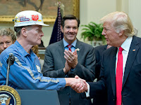 Photograph of President Trump shaking hand of hard-hat-wearing coal miner (Photo Credit: Ron Sachs/Getty Images) Click to Enlarge.