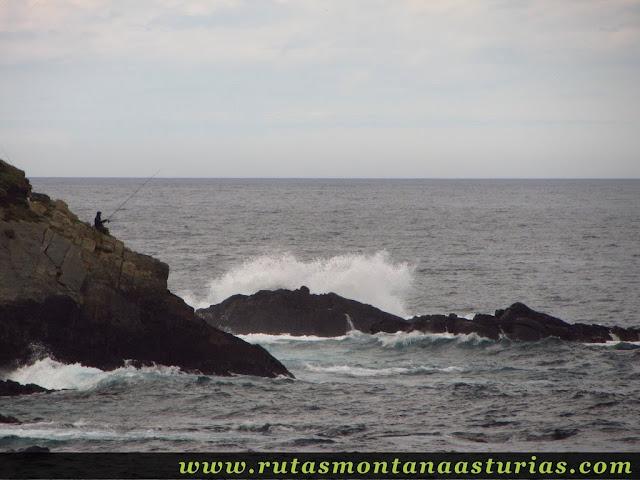 Pescador pescando en roca sobre el mar cantábrico