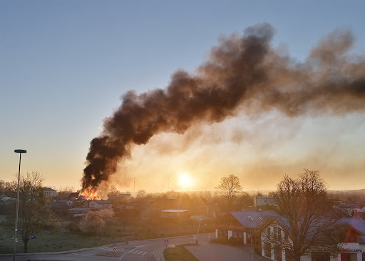 Liesmas un dūmi no ugunsgrēka saullēkta laikā