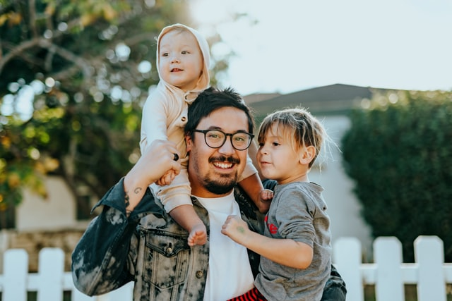 a dad holding two children in front of a new house, representing kid-friendly features most home buyers overlook