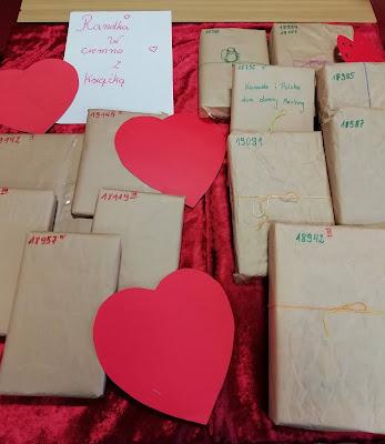 """Książki obłożone papierem pakownym leżą na czerwonym materiale, dookoła czerwone serca oraz kartka z napisem """"Randka w ciemno z książką"""""""