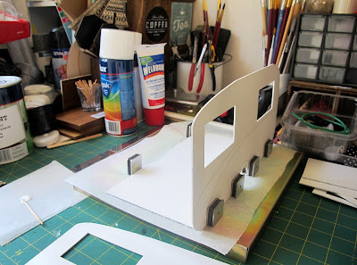 Dolls' house retro caravan kit side being glued to the base.