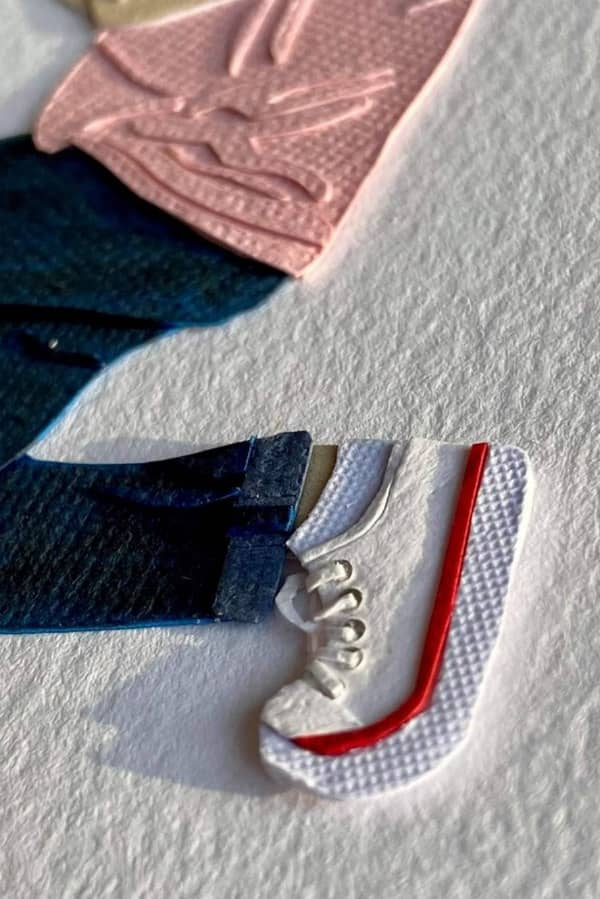 detail of paper art figure wearing blue jeans and white sneaker