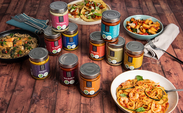A collection of sauces and different meals that you can make with the sauces. There is cutlery on napkins scattered across a wooden table with bowls of spaghetti, tacos and rice scattered around