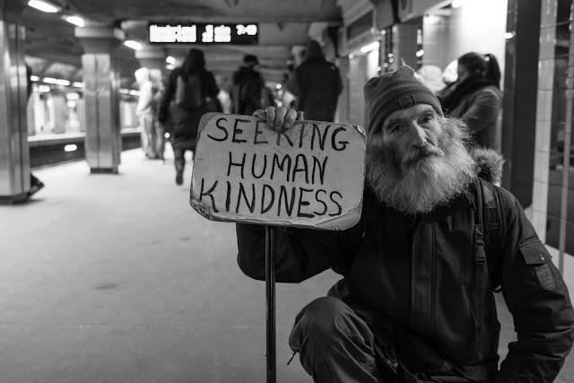 homeless man begging in subway station with a sign