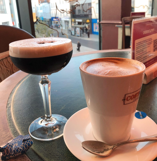 A coffee and espresso martini on a table overlooking a high street