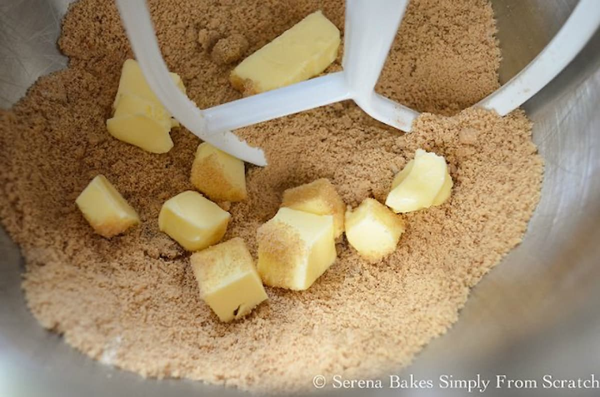 Cubed Butter added to brown sugar and flour mixture in a mixing bowl fitted with a paddle attachment.