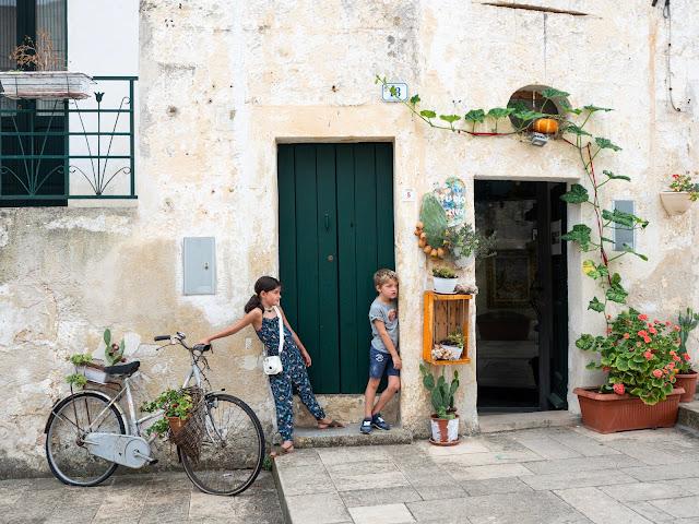 Niños apoyados en una puerta verde con bici y cactus
