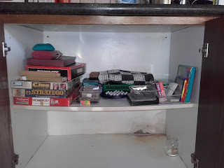 games cupboard with damp patch at the bottom