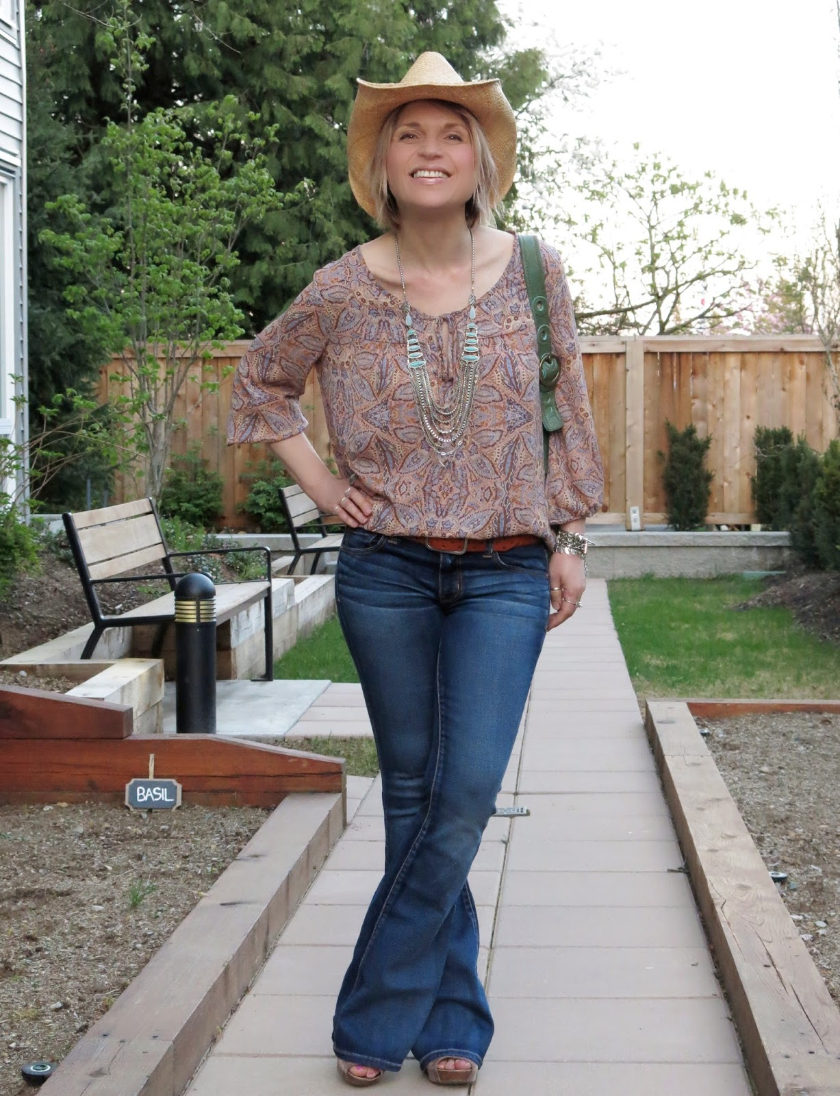 styling flare jeans with a paisley blouse and cowboy hat