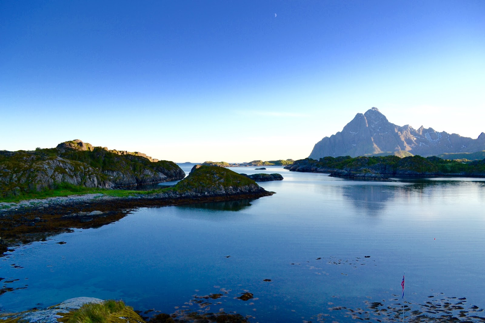 The indescribable tranquil settings and natural splendor of the Lofoten Islands in northern Norway will surely captivate all who visit. This photo taken at 11:00 p.m. from a lookout platform perched upon the bluff overlooking above Nyvågar Rorbuhotell.