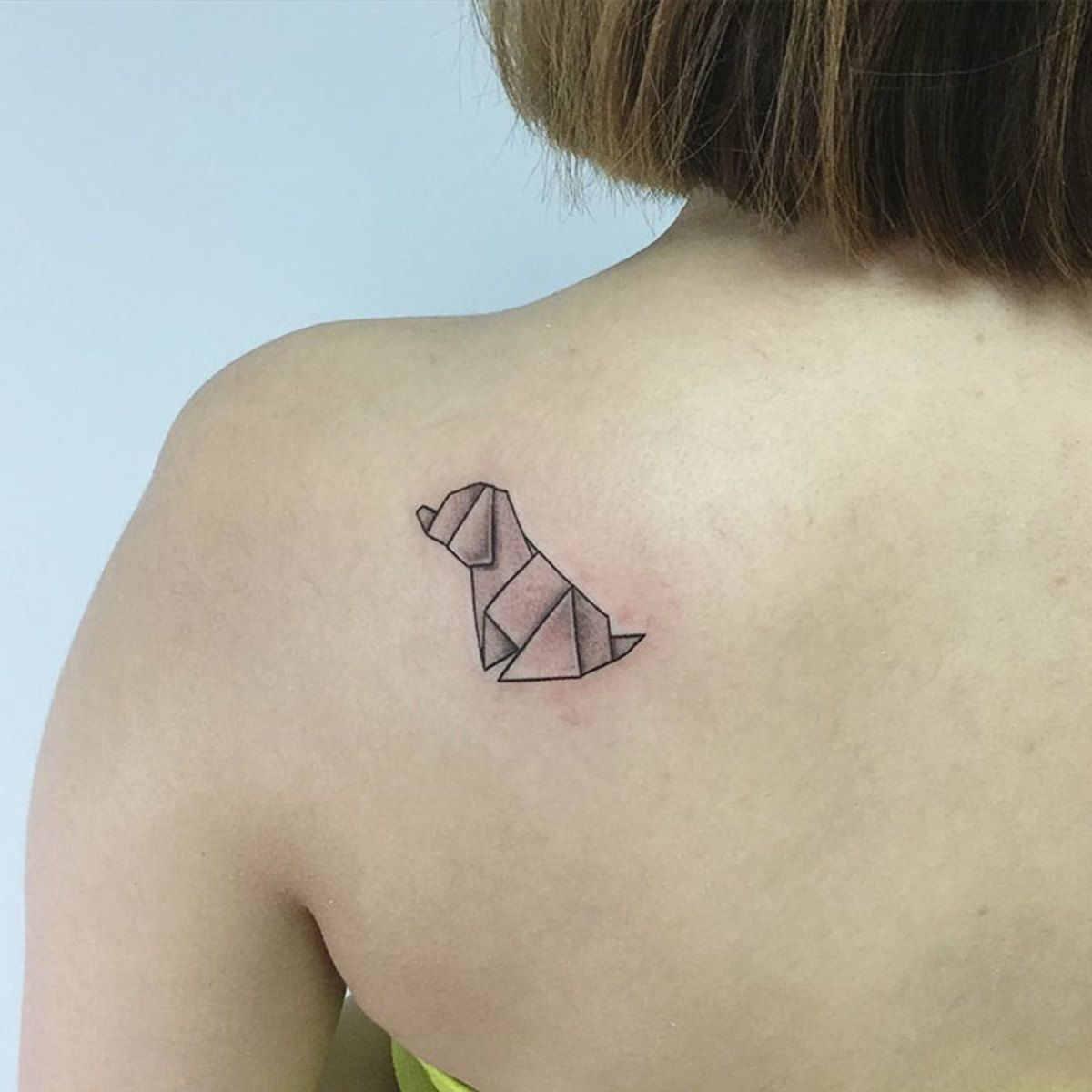 foto de un tatuaje pequeño de perro origami en el omóplato