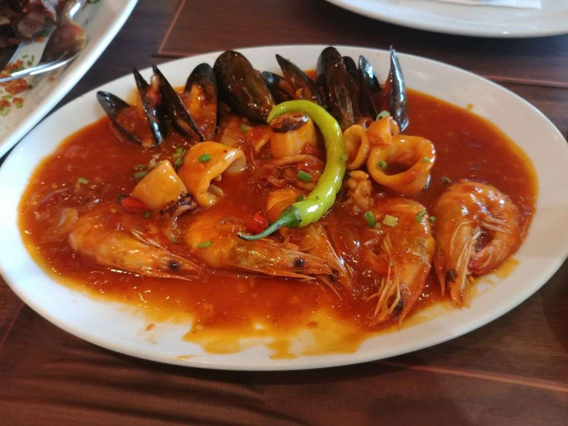 An appetizer of mixed shrimps, mussels, and squid in red chili sauce at Mesa Filipino Moderne