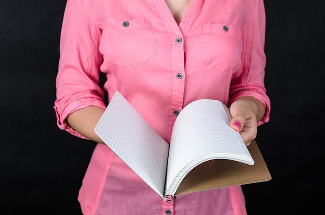 wanita berbaju pink sedang memegang buku catatan
