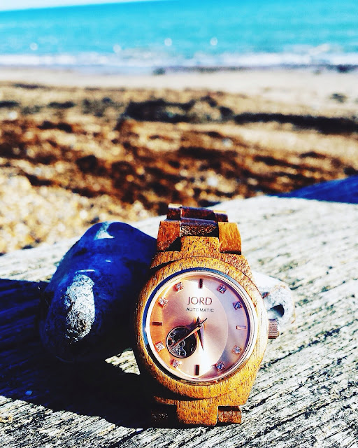 Jord wooden watch on a beach with blue sea