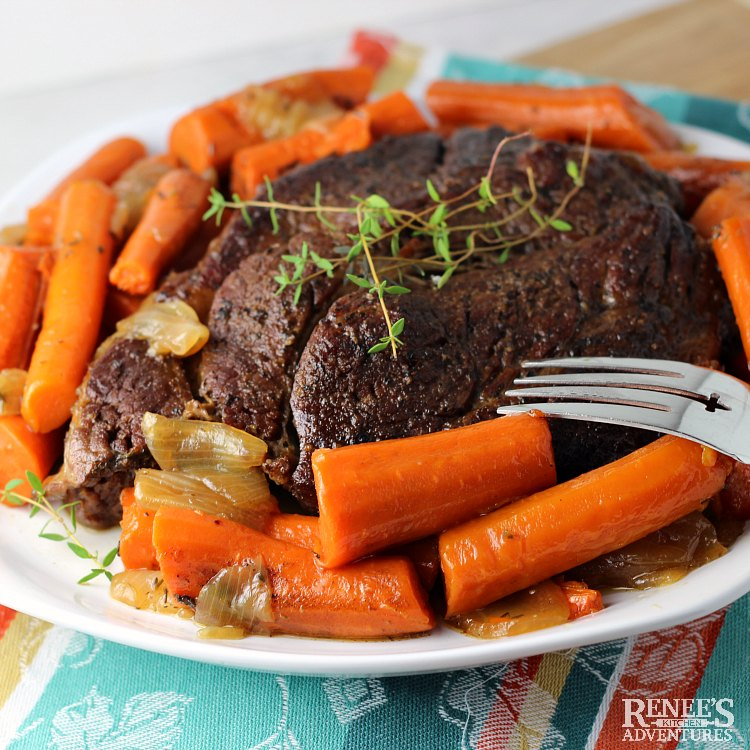 Dutch Oven Pot Roast by Renee's Kitchen Adventures on platter with carrots and onions and garnished with fresh thyme