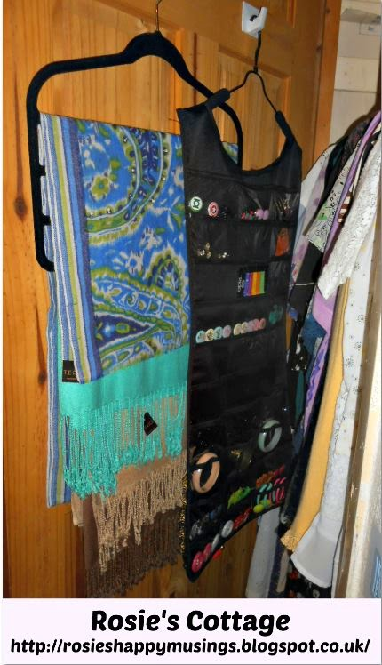 "Hooks fitted to the inside of the closet door are home to pashmina scarves organized onto their multi level hanger and a ""dress"" shaped hanging jewellery organizer."