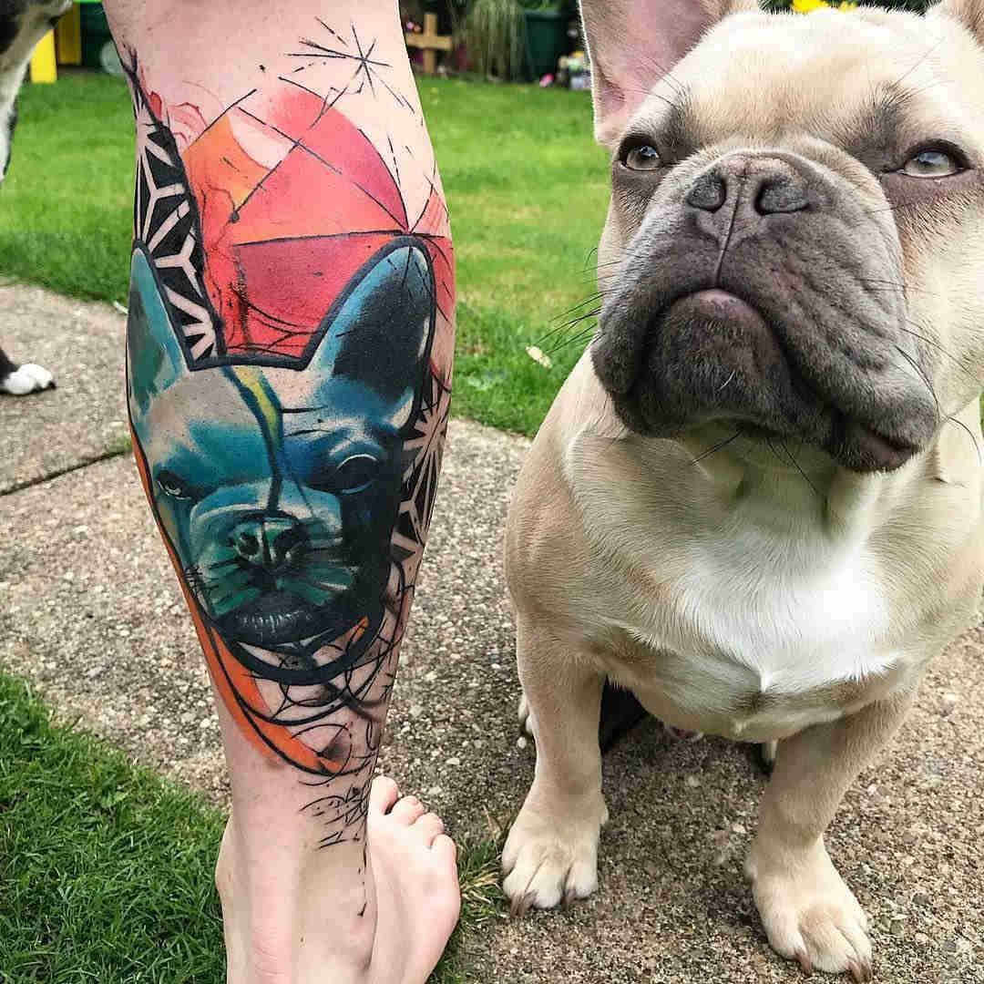 Vemos la imagen de un bulldogo posando junto a  su dueño que luce un tatuaje en homenaje a su perro