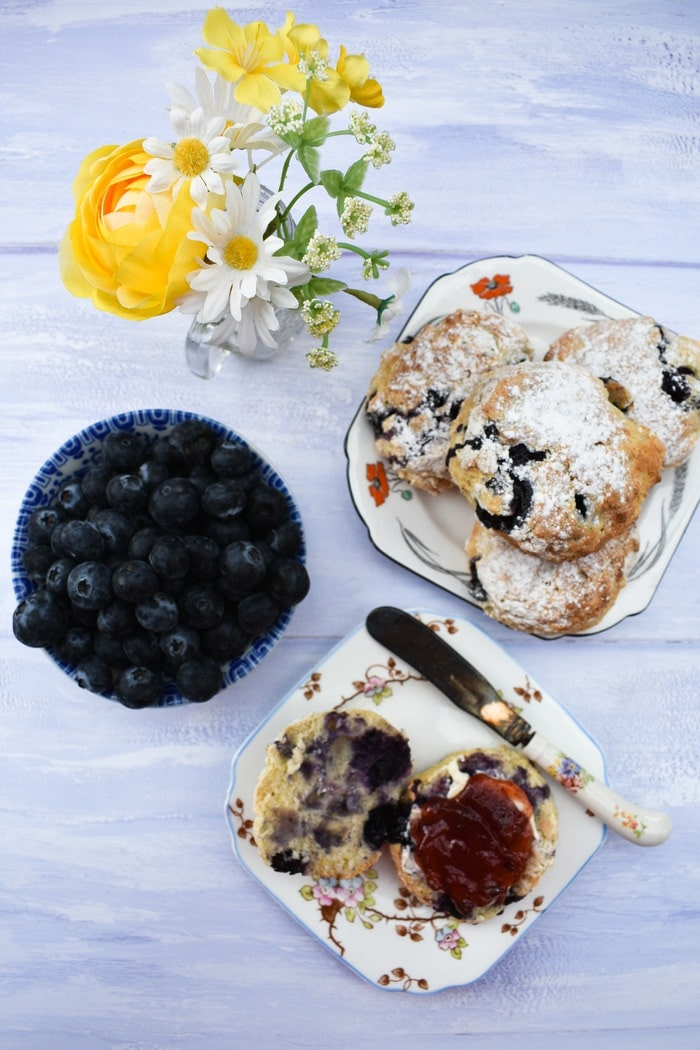 Overhead view of Blueberry Lemonade Scones, a bowl of blueberries and jar of  flowers