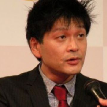 Japanese guy novelist Noburo Yamaguchi wearing format suit and red tie speaking to a microphone
