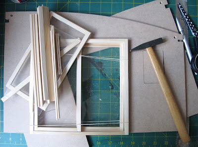 Two side walls of a dolls house kit, with holes cut for sliding doors and pieces of wood inserted into previously-cut window openings.