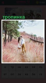 на тропинке стоит пара влюбленных и целуется среди цветов
