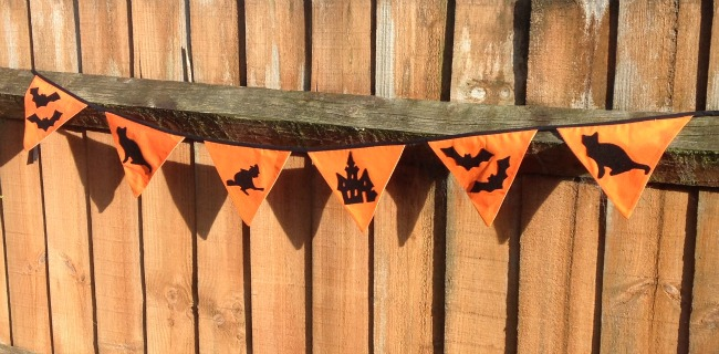 Orange bunting with black silhouettes of cat, bats, old house and witch