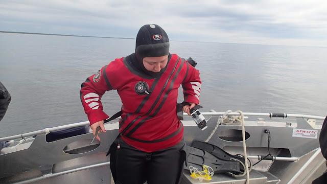 Sukeltaja pukee painovyötä kuivapuvun päälle veneessä tyynellä kelillä